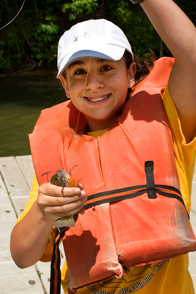 boy holding fish at wildlife camp