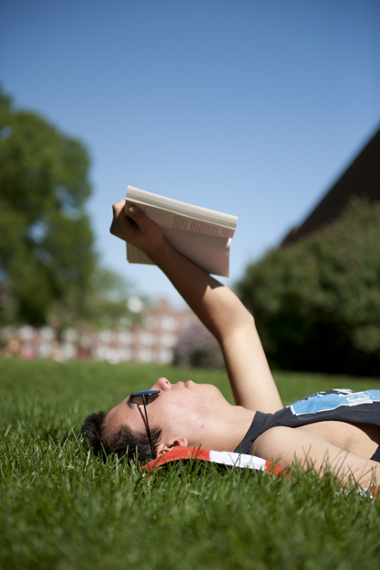 Student laying on grass reading a book.