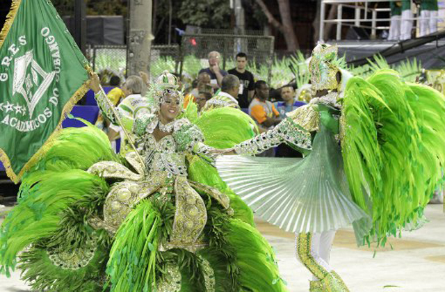 Two people on parade dressed in bright green carnaval costumes