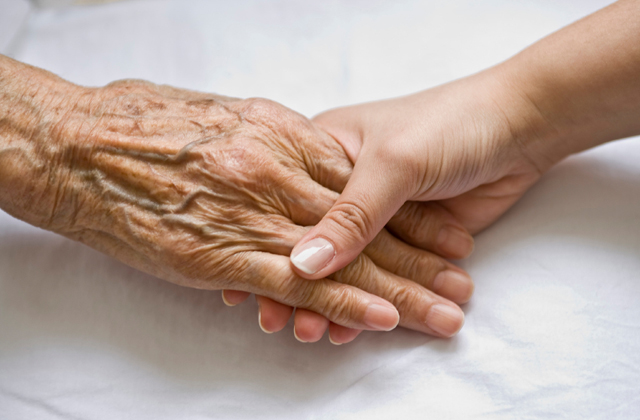 hand of a younger person holding the hand of an elderly person