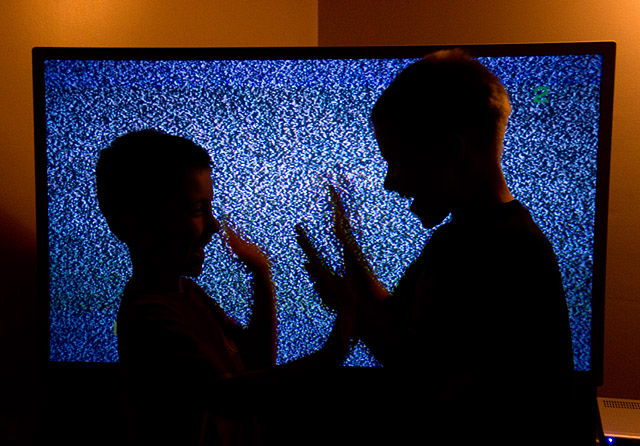 two children playing in front of a television screen