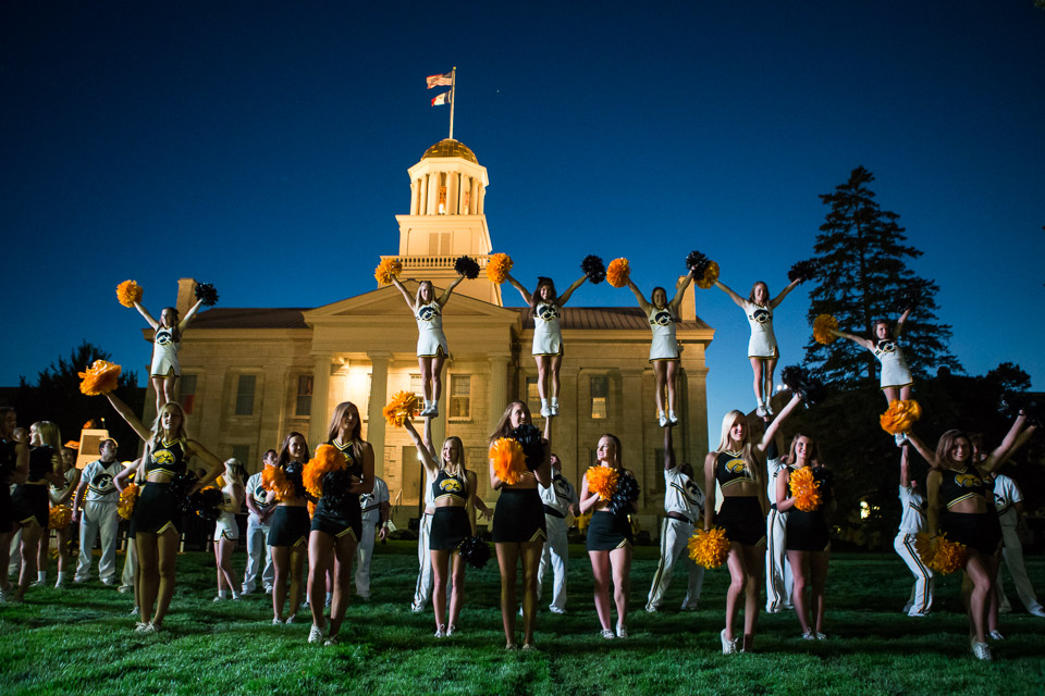 A group of male and female cheerleaders performing in front of a building