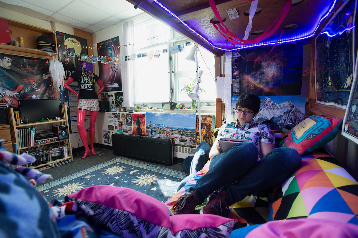 Student reading on couch in decorated dorm room