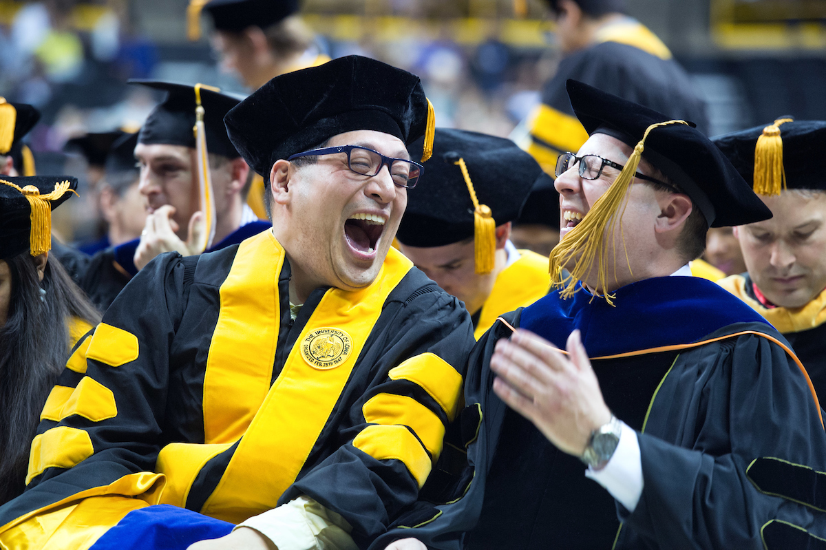 Graduate and professor laughing together at commencement ceremony