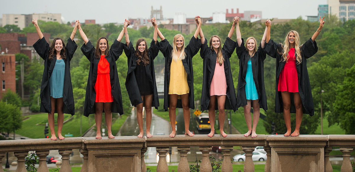Women in graduation gowns standing near Old Capitol holding raised hands