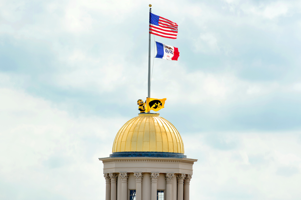 Herky atop Old Capitol holding Hawkeye flag