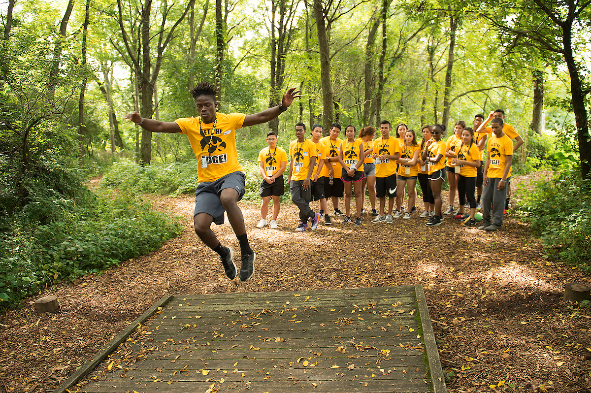 Student in gold t-shirts completing an exercise in wooded area