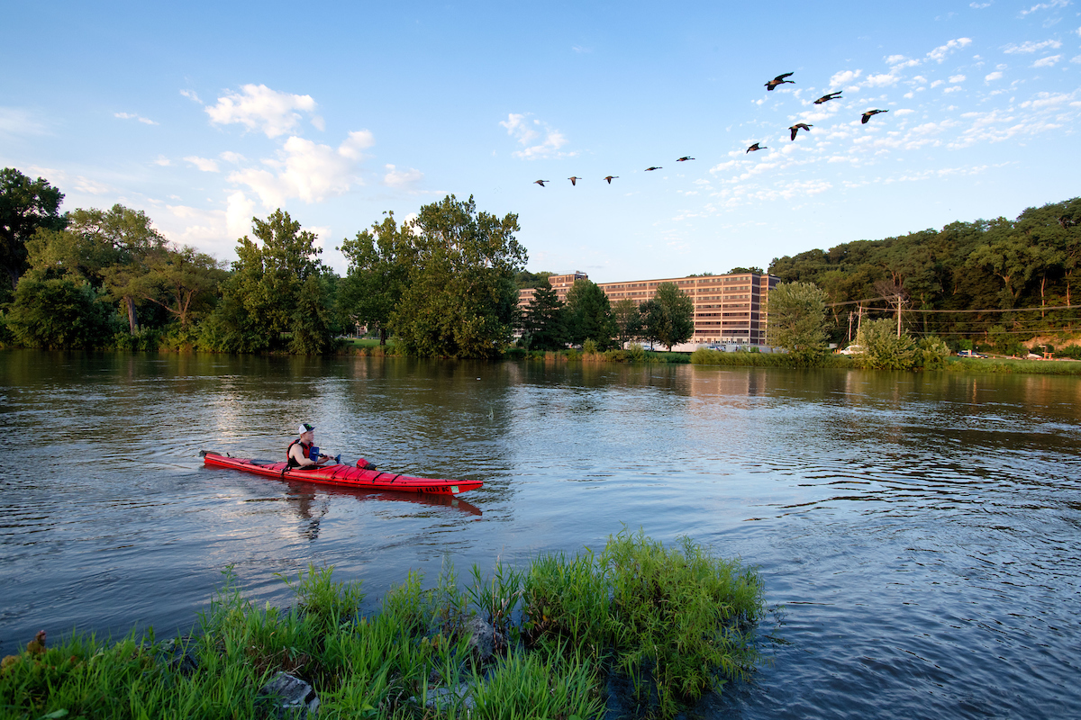 Canoe on river with geese and Mayflower Hall in background