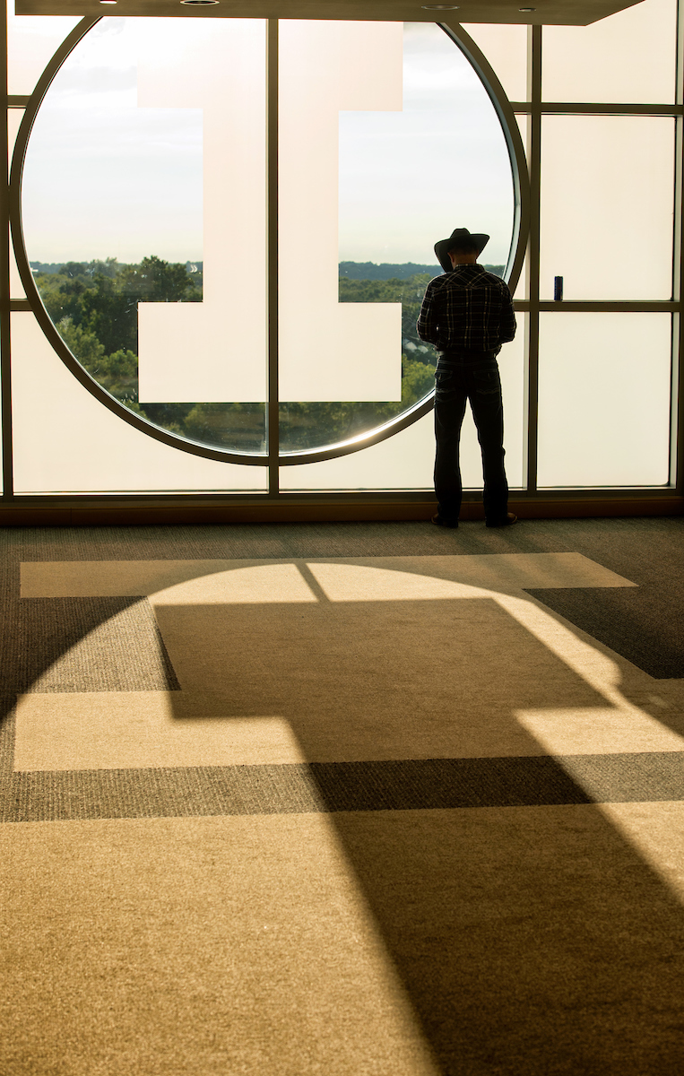 Man in cowboy hat silhouetted by light coming through large window