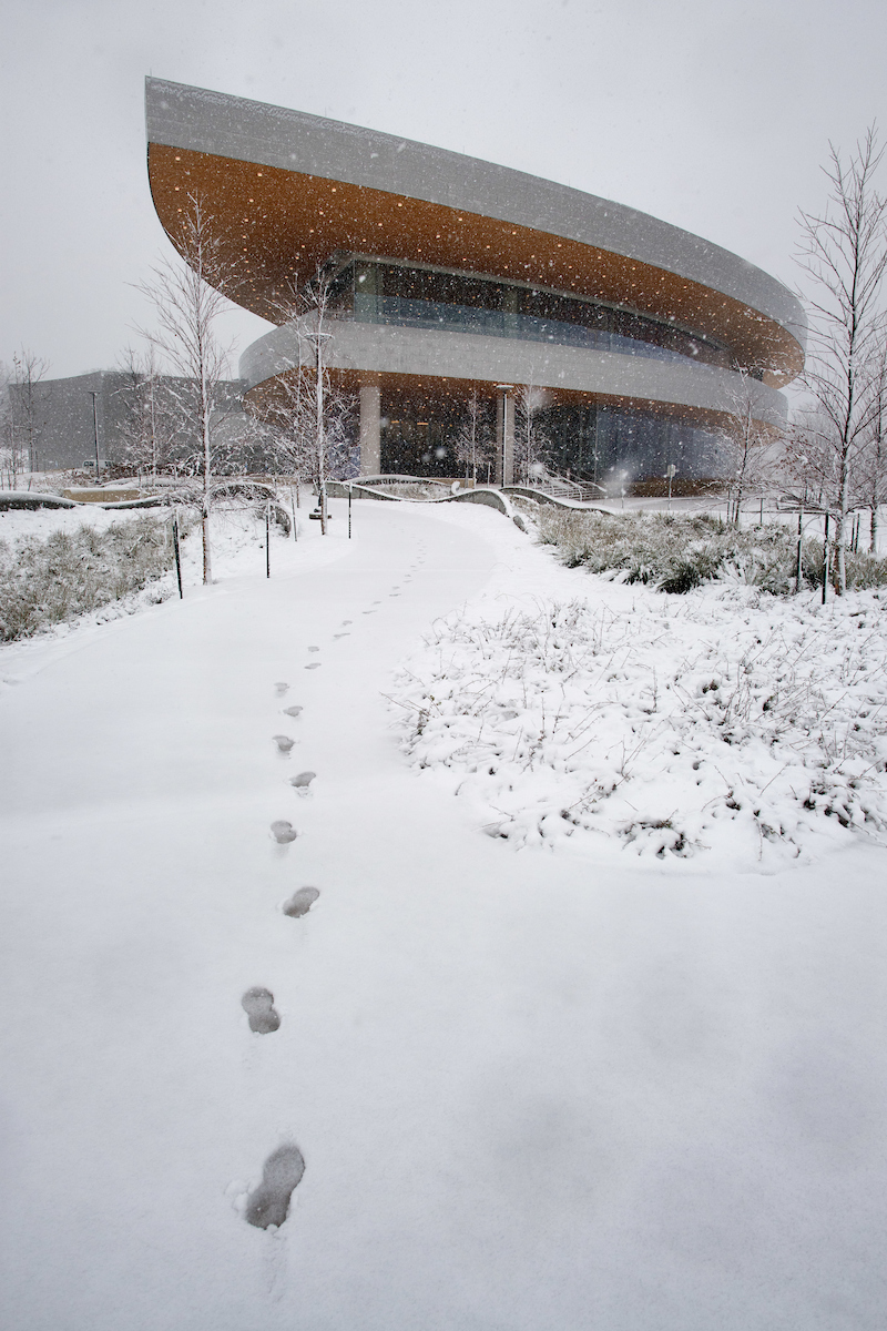 Footprints in snow leading up to Hancher Auditorium