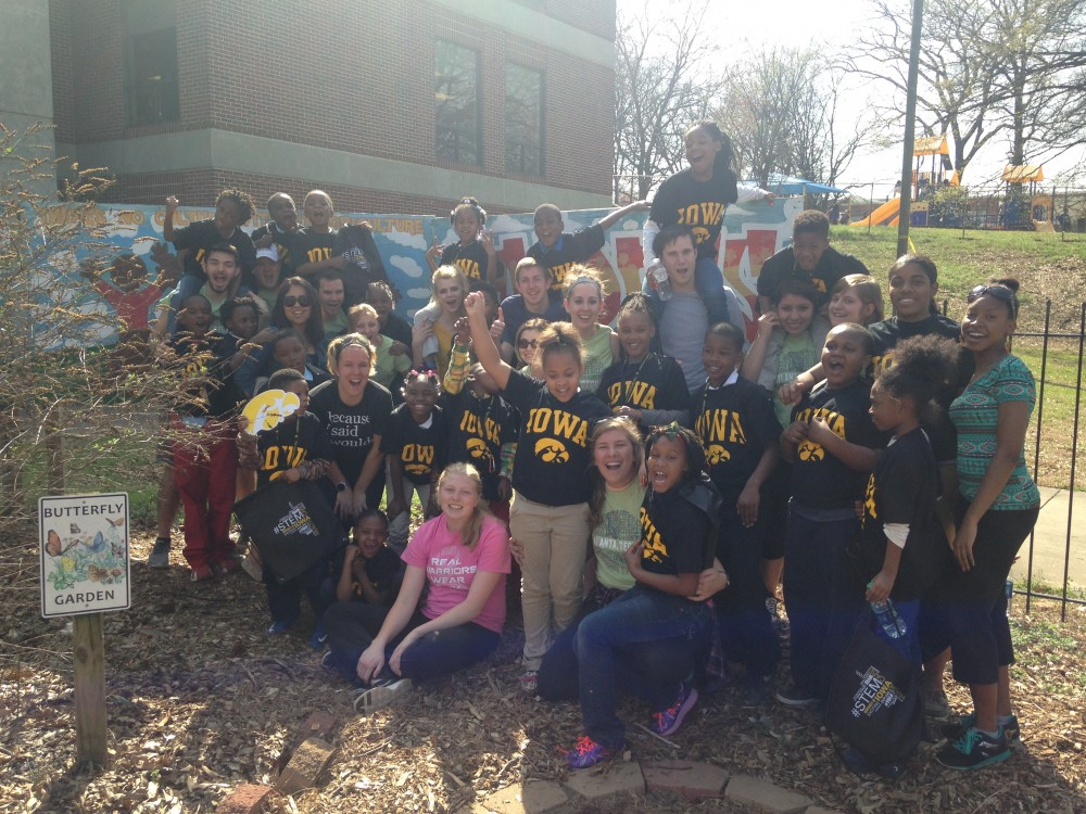 """A group of students stand by a butterfly garden while yelling, \""""Go Hawks!\"""""""