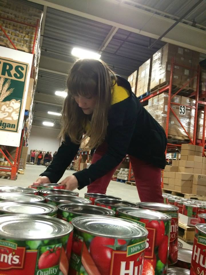 A UI female student leans over to help pick up cans of Hunts tomato  sauce to help distribute them to those in need.