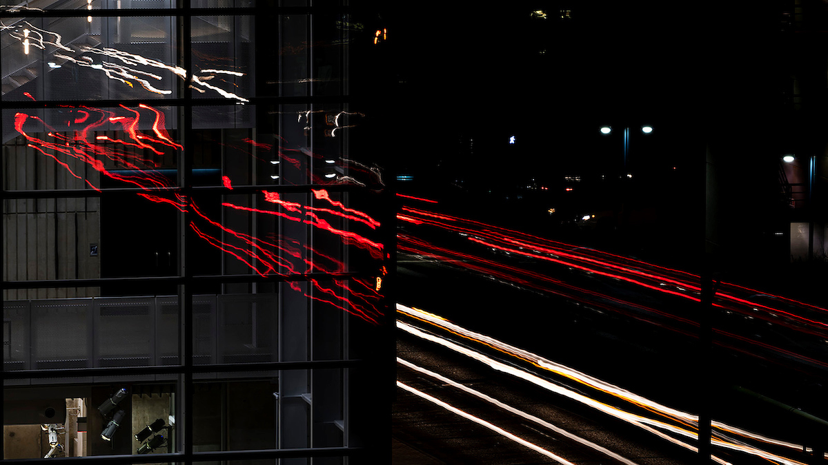 Traffic lights at night reflected in music building's glass exterior