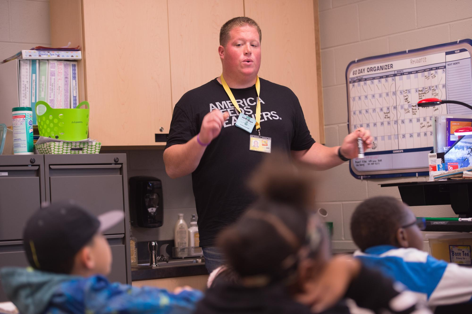 Student teacher Reid Kallberg works with students in a classroom.