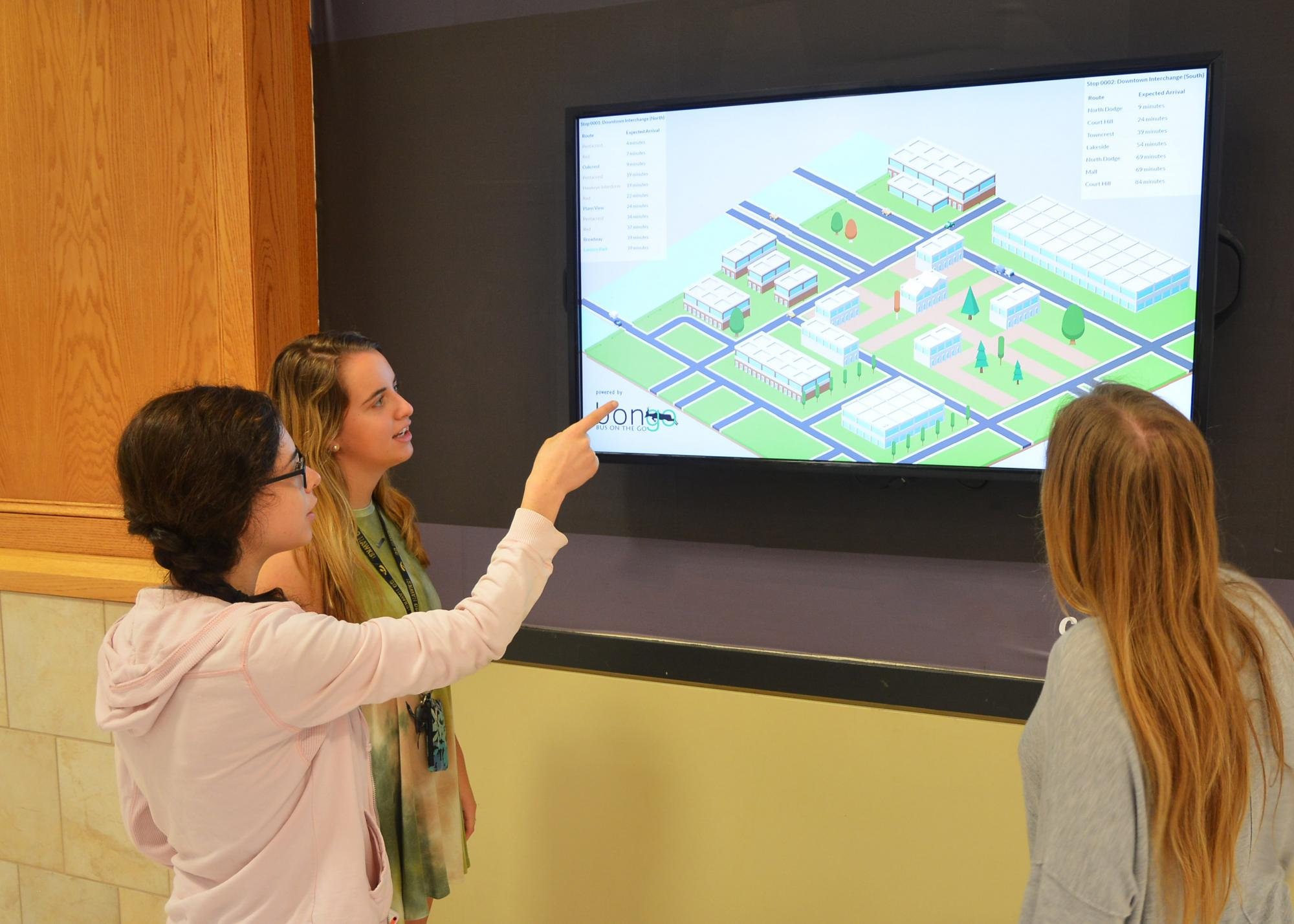 women looking at and pointing at digital signage