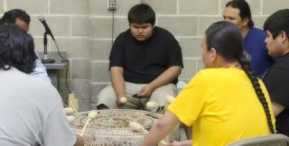 Members of Native Youth Standing Strong take part in a drum circle.