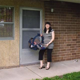 Color photo of Anne Wilmoth posing outside the door of her Hawkeye Court apartment holding her newborn baby in a carseat