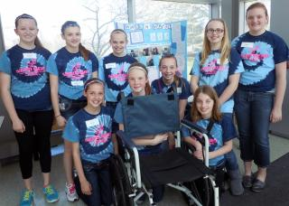 A team of nine girls from Titan Hill Intermediate School in Council Bluffs pose with their 2013 award-winning invention, the Walk n' Wheel.