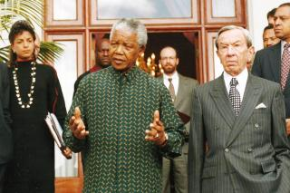 Susan Rice, Nelson Mandela, and Secretary of State Warren Christopher emerge from a meeting after negotiations witih Ron McMullen in the background.