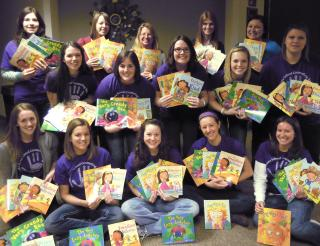 Professor Carol Klose Smith and 14 school counseling students hold the colorful children's books they donated.