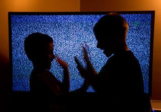 children playing in front of static-filled tv