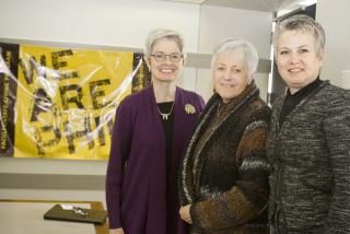 Lynette Marshall, Sally Mason, and Sarah Gardial pose in front of a We Are Phil poster