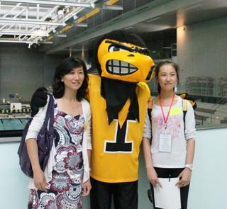 student and staff member pose with Herky in wellness center