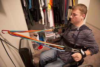 Travis strengthens his arms and shoulders with exercise bands.