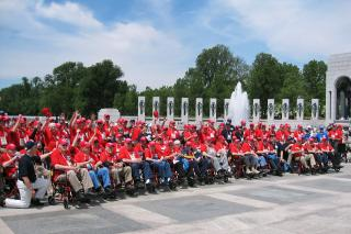 Group of veterans in matching shirts at World War II Memorial.