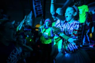 A young girl in a tye-dyed t-shirt and tutu dances with the letters FTK painted on her cheek.