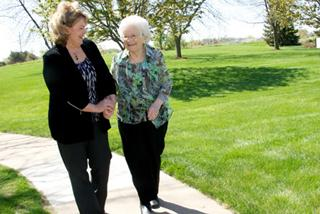 Karen Arthur and Alma Olson walk along a path