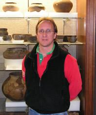 A man standing in front of a display of pottery