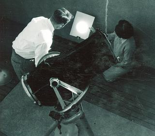 Two people working inside a campus observatory