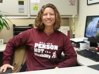 "Carly Armour sits at her desk, wearing a ""See the PERSON, NOT the disability"" t-shirt"