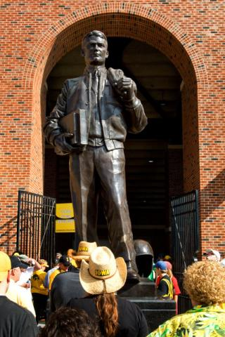 Color photo of football fans looking up at a bronze statue of Nile Kinnick
