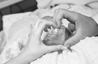 a man's hand and a woman's hand forming the shape of a heart around their child's feet