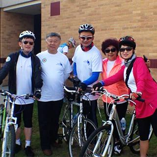 a group of Chinese visitors stand with their bikes