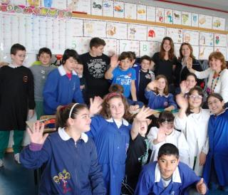 A classroom full of students poses waving at camera