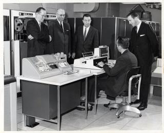 1961 black-and-white photo of computer center director demonstrating new IBM computers to four men