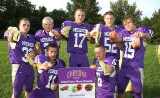 football team holding healthy food items