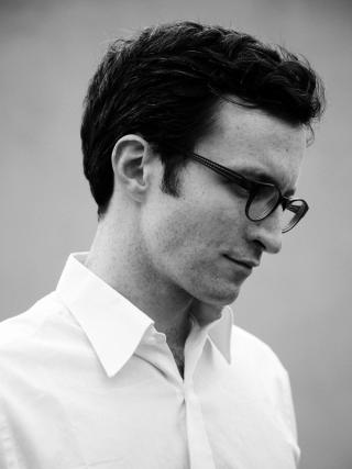A photo of a young man wearing black glasses and a white shirt