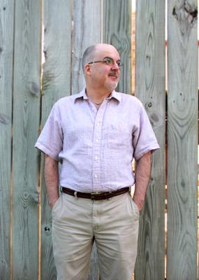 A man with his hands in his pants pockets standing in front of a wooden fence