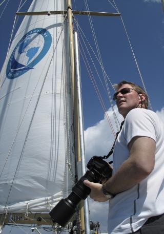 Photo of a man holding a camera in front of a sail on a sailboat