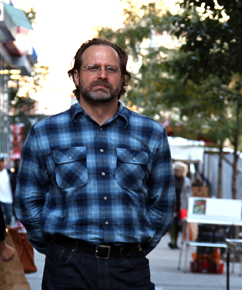 Photo of a bearded man in a blue flannel shirt