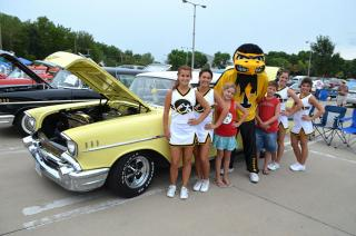 Herky and cheerleaders pose next to a vintage car