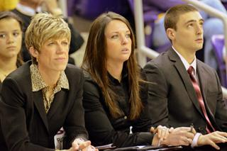Abby Emmert (center) sits courtside at a UI women's basketball game
