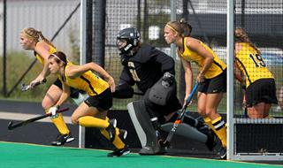 field hockey players in front of goal