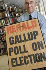 man in UI library holding Herold Gallup Pool on Election poster
