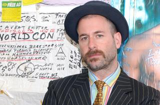 kenneth goldsmith standing before wall with writing