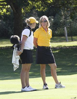 UI head women's golf coach Megan Menzel talks with one of her players on the golf course.